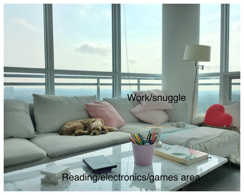 Image of a high-rise condo, almost 360-degree skyline view of Toronto. Cocker spaniel dog sleeps peacefully on a large white L shaped sofa with iMac and headphones next to him demonstrating versatile workspace in the home.